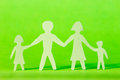 Family cutout shape against green background Royalty Free Stock Images