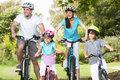 Family on cycle ride in countryside smiling Royalty Free Stock Photos