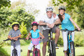 Family on cycle ride in countryside smiling to camera Royalty Free Stock Photos