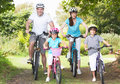 Family on cycle ride in countryside smiling to camera Royalty Free Stock Photo