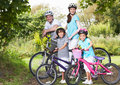 Family on cycle ride in countryside smiling to camera Royalty Free Stock Photography