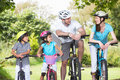 Family on cycle ride in countryside smiling to each other Royalty Free Stock Image