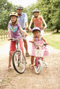 Family Cycling In Countryside Wearing Safety Helme Royalty Free Stock Photo