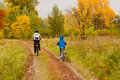 Family cycling outdoors, golden autumn in park Stock Images