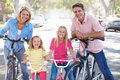 Family cycling on suburban street smiling to camera Stock Images