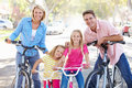 Family cycling on suburban street smiling to camera Stock Image