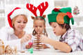 Family decorating the gingerbread christmas tree Royalty Free Stock Images