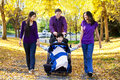 Family with disabled child in wheelchair walking among autumn le
