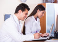 Family doctors with stethoscope working in office together Royalty Free Stock Photo