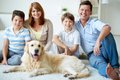 Family with dog portrait of happy their pet having rest at home Stock Images