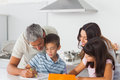 Family drawing together in kitchen at home Royalty Free Stock Photos