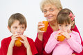 Family drinking juice happy grandmother with grandchildren fruit Stock Photography
