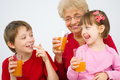 Family drinking juice happy grandmother with grandchildren fruit at home Royalty Free Stock Image