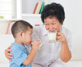 Family drinking milk happy multi generations asian at home beautiful grandmother and grandson healthcare concept Stock Images