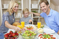 Family Eating Healthy Food & Salad At Dining Table Royalty Free Stock Photo