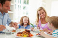 Family eating meal at home together sitting around table smiling each other Royalty Free Stock Photography