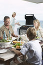 Family enjoying a barbecue at seaside sitting around table eating barbecued food with mother standing grill grilling Stock Photography