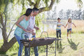 Family enjoying barbeque by lake Royalty Free Stock Images