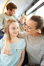 Family enjoying bus journey together looking at out each other smiling Royalty Free Stock Photos