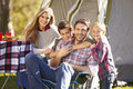 Family enjoying camping holiday in countryside smiling to camera Royalty Free Stock Images