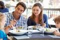 Family enjoying meal at outdoor restaurant smiling Stock Photos