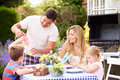 Family enjoying outdoor barbeque in garden with father pouring glass of juice Stock Photo