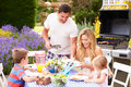 Family enjoying outdoor barbeque in garden having a good time Royalty Free Stock Image