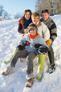 Family Enjoying Sledging Down Snowy Hill Stock Photography