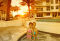 Family enjoying tropical resort vacation as the sun sets in the background a enjoys some fun moments together at a swimming pool Royalty Free Stock Photography
