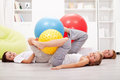Family exercising with large gymnastic balls laying on the floor at home Stock Photos