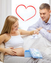 Family expecting child with gift box and bootees Stock Images