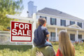 Family facing for sale real estate sign and house curious beautiful new Stock Photo