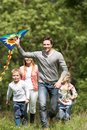 Family flying kite in countryside smiling Stock Image
