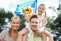 Family flying kite in countryside smiling to camera Royalty Free Stock Image