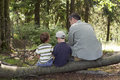 Family in forest grandfather with children sitting and resting on a log Royalty Free Stock Images