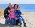 Family of four at the beach Royalty Free Stock Images