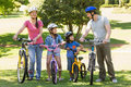 Family of four with bicycles in park full length a the Royalty Free Stock Images