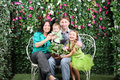 Family of four with bunch of flowers sit on bench in garden near verdant hedge Stock Photos