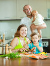 Family of four cooking red fish at home kitchen happy Stock Images