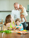 Family of four cooking salmon fish at home kitchen happy Stock Photos
