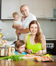 Family of four cooking salmon happy fish at home Stock Photography