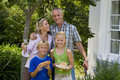 Family of four in garden woman with glass of wine boy and girl with burgers smiling portrait women Royalty Free Stock Photo