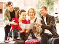 Family of four with luggage checking direction in map Royalty Free Stock Photo