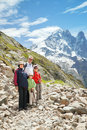 The family from four persons staying on trail in mountains stone against mountain summits Royalty Free Stock Image