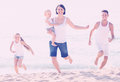 Family of four running on sandy beach on sunny weather