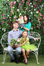 Family of four sit on white bench with bunch of flowers in garden near verdant hedge Stock Photo