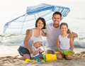 Family of four sitting together under beach umbrella on beach