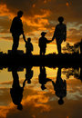 Family of four sunset water Royalty Free Stock Photo