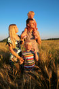 Family of four on sunset wheaten field Royalty Free Stock Photo