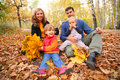 Family of four with yellow leaves sits in wood Royalty Free Stock Photo